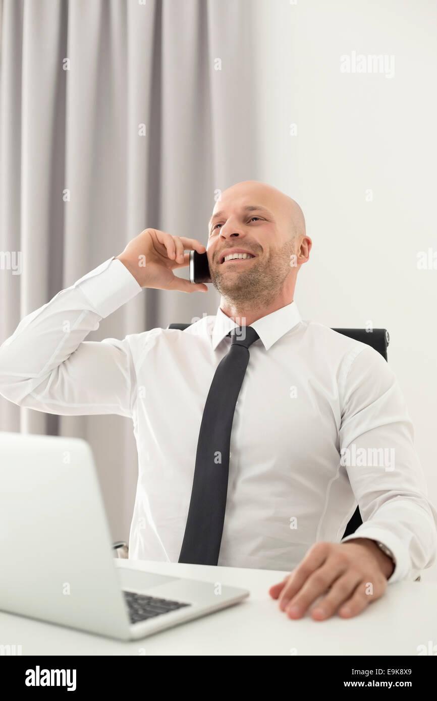 Adulto medio imprenditore su chiamata in home office Immagini Stock
