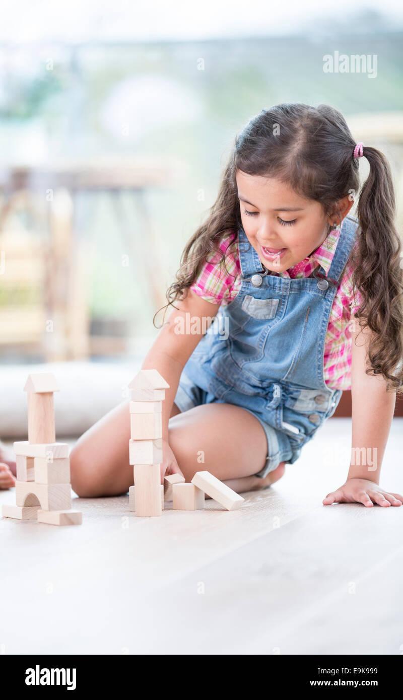 Bambina di blocchi di costruzione mentre è seduto sul pavimento di legno duro Immagini Stock