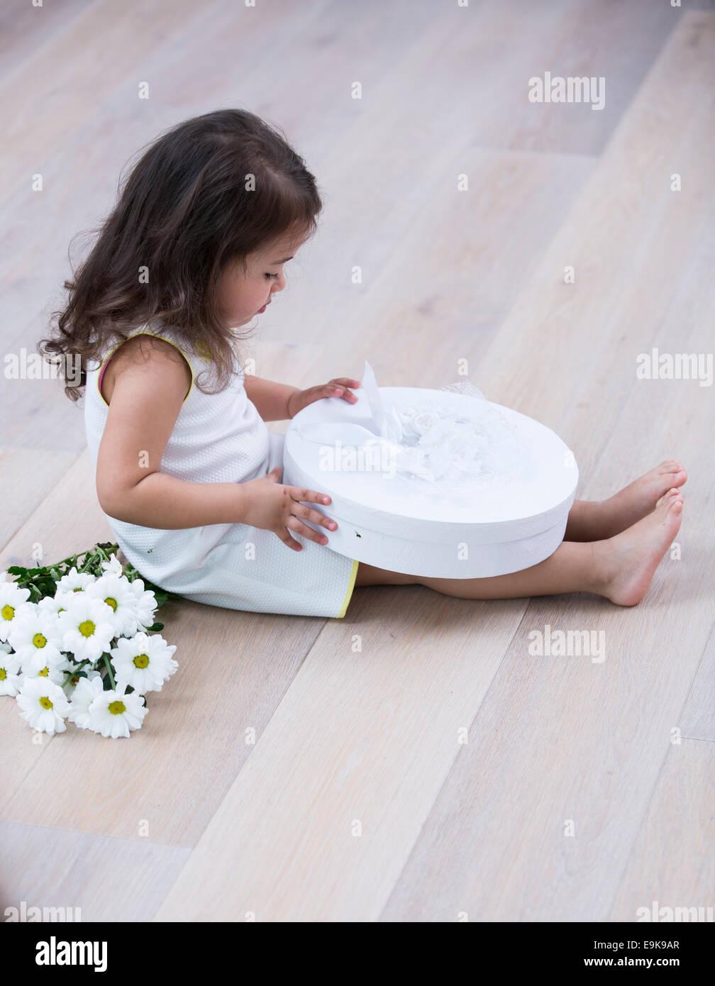 A piena lunghezza lato della bambina apertura scatola regalo sul pavimento a casa Immagini Stock