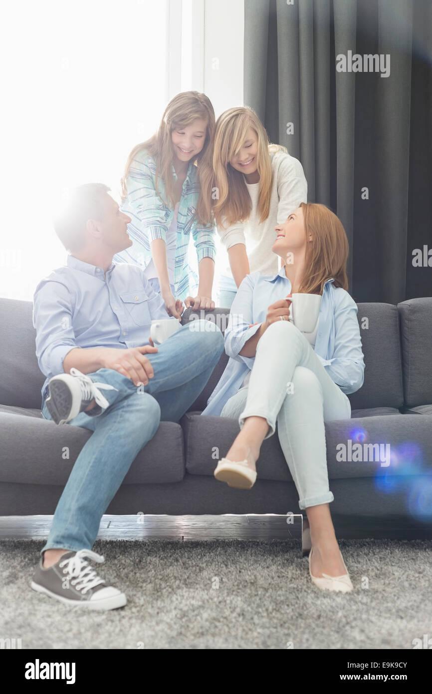 Genitori felici con le figlie trascorrere del tempo di qualità nel soggiorno Immagini Stock