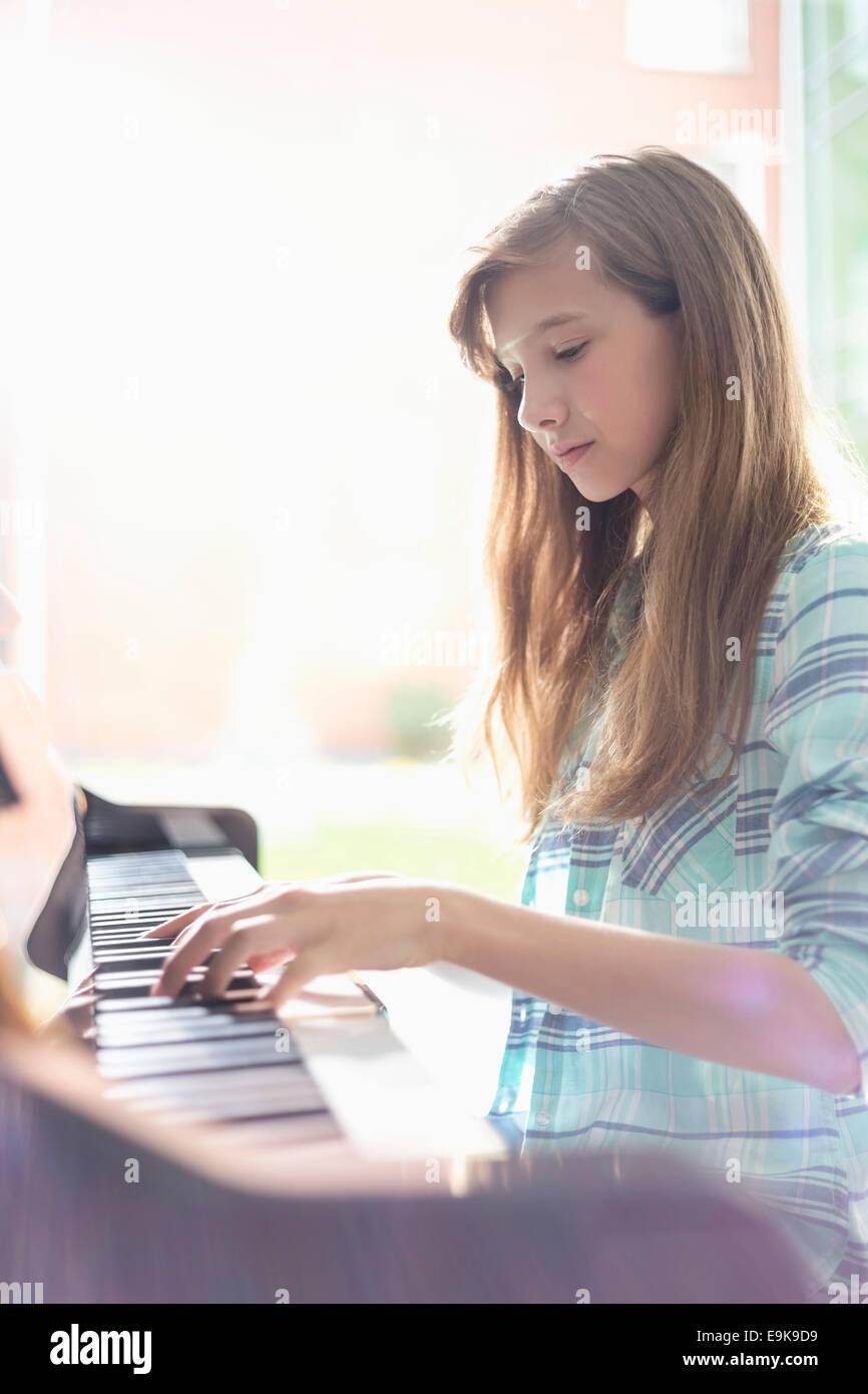 Vista laterale di una ragazza suonare il pianoforte a casa Immagini Stock