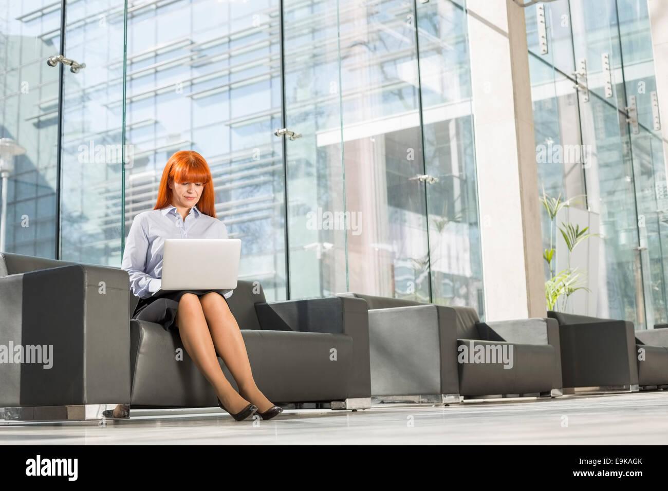 Lunghezza intera di mezza età imprenditrice utilizzando il portatile in ufficio lobby Immagini Stock