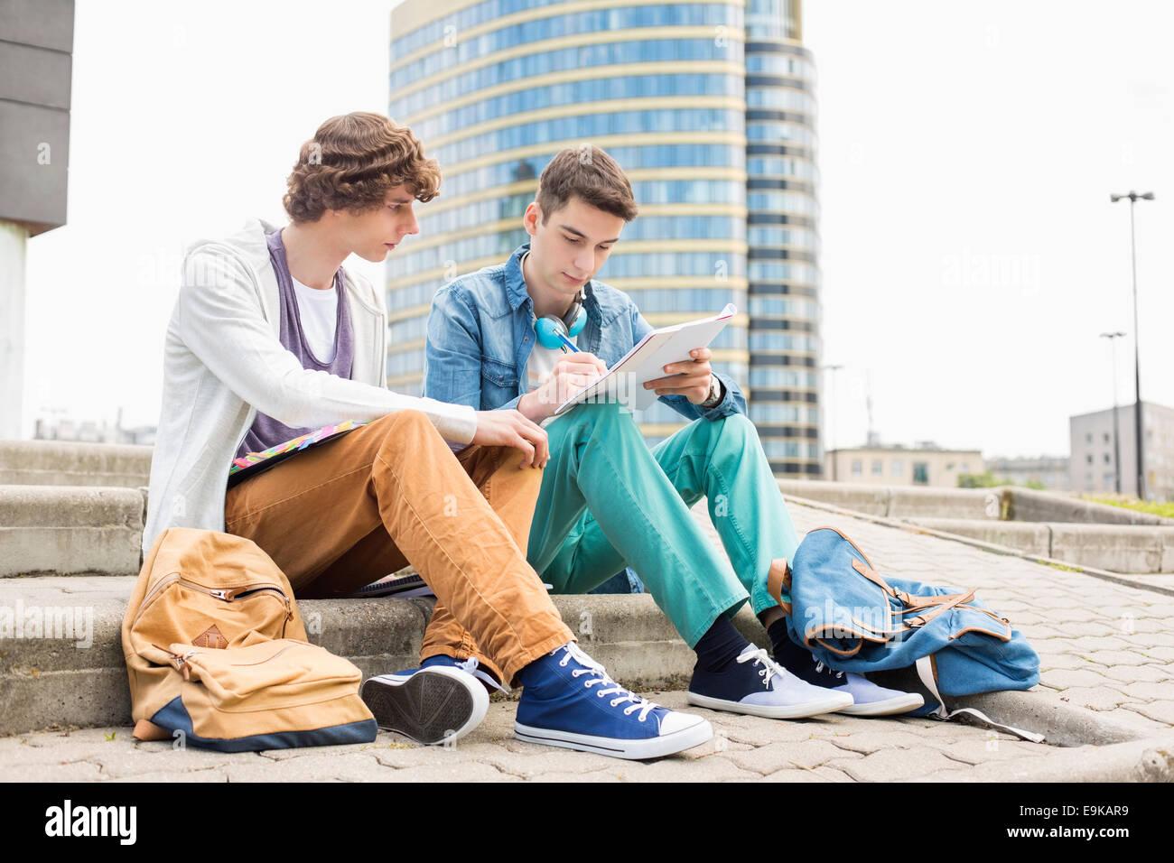 Lunghezza completa di maschi giovani studenti universitari che studiano sui gradini contro un edificio Immagini Stock