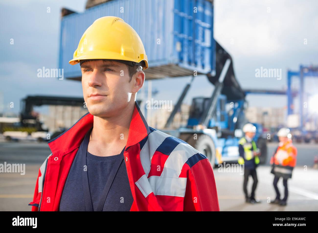 Fiducioso lavoratore di sesso maschile con i colleghi in background in cantiere di spedizione Immagini Stock