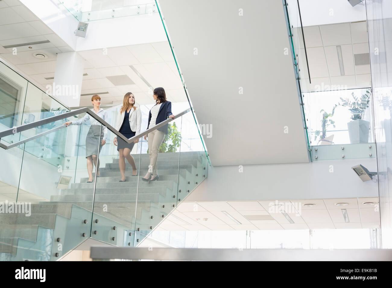 Imprenditrici a conversare mentre si sta spostando verso il basso le fasi in office Immagini Stock