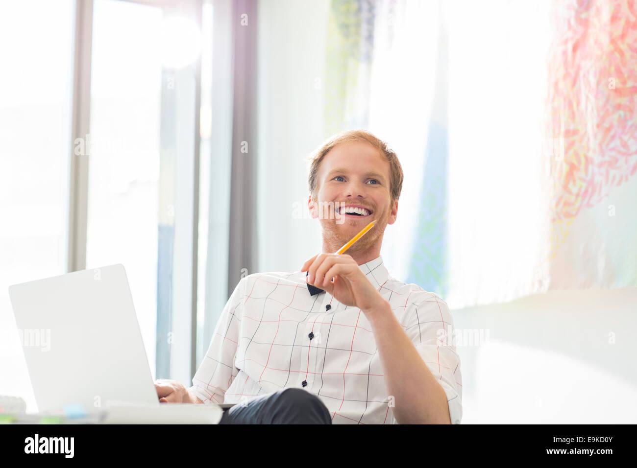 Happy businessman che guarda lontano mentre è seduto alla scrivania in ufficio creativo Immagini Stock
