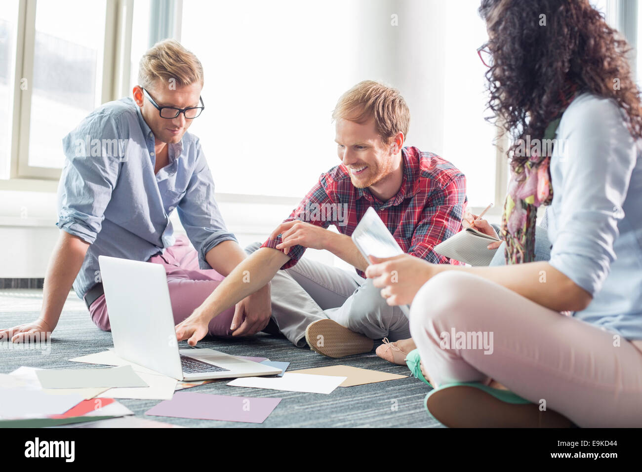 Imprenditore spiegando piano sul laptop per i colleghi in ufficio creativo Immagini Stock