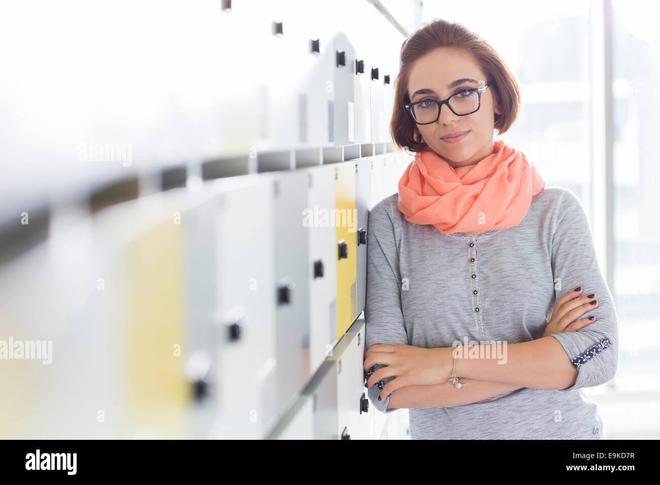 Ritratto di fiducioso imprenditrice in piedi con le braccia incrociate in spogliatoio presso il creative office Immagini Stock