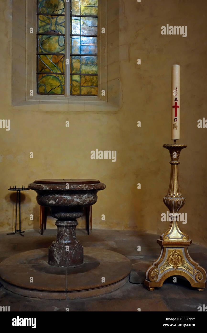 Fonte battesimale e il cero pasquale nella cattedrale di Nevers / Cathédrale Saint-Cyr-et-Sainte-Julitte de Immagini Stock