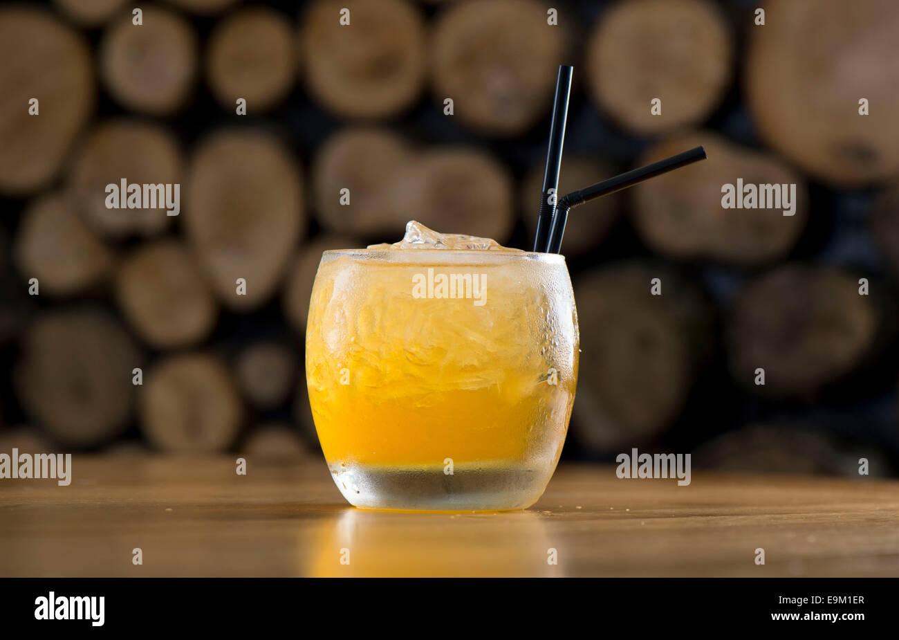 Un Giallo mango orange cocktail drink con una cannuccia. Immagini Stock