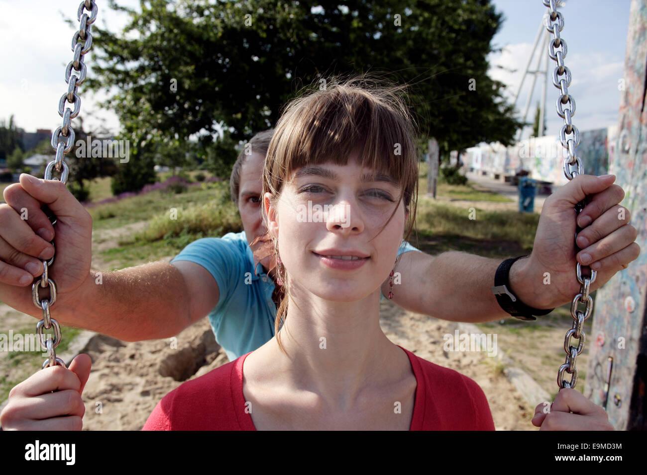 Uomo Donna di spinta sul parco giochi swing Immagini Stock