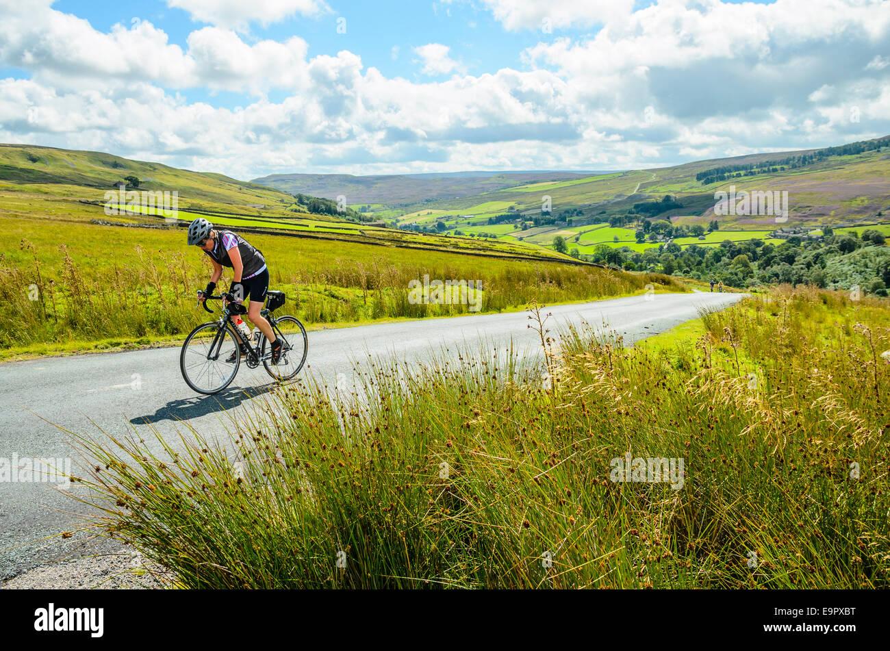 Ciclista femmina scalata del Stang nel Yorkshire Dales Immagini Stock