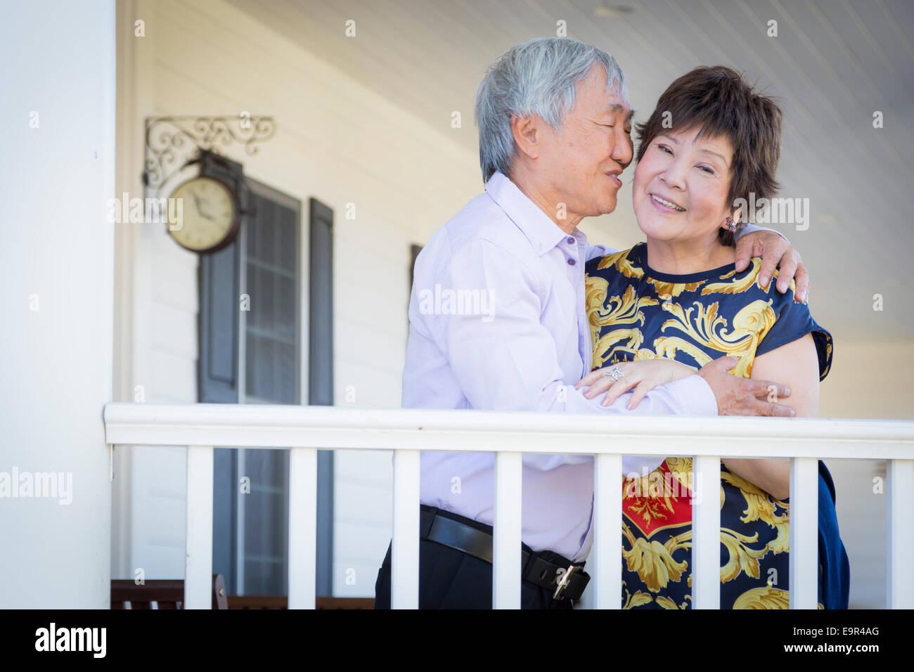 Attraente felice coppia cinese godendo la loro casa all'esterno. Immagini Stock