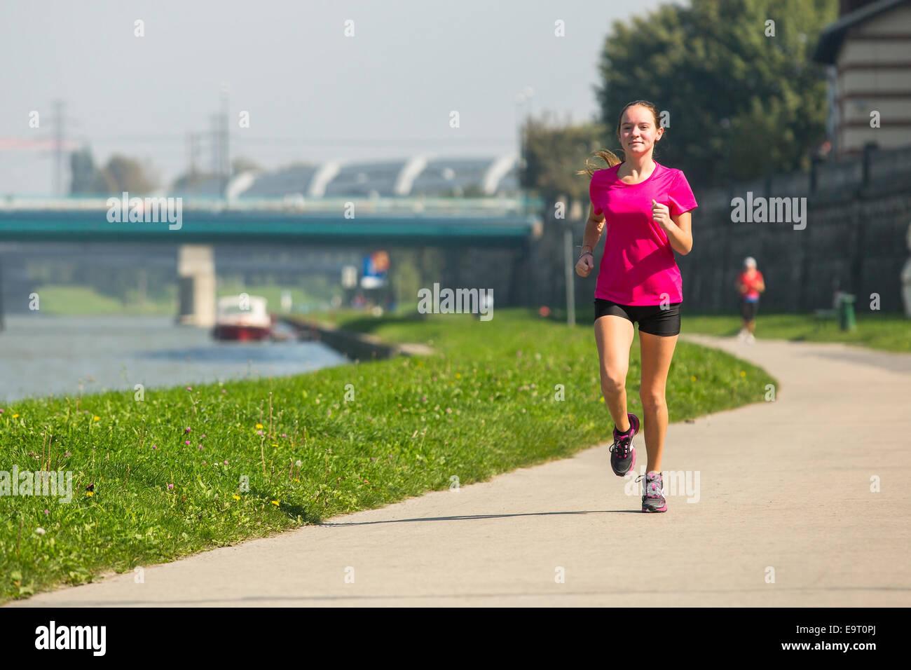 Ragazza giovane jogging vicino il greto del fiume. Uno stile di vita sano. Immagini Stock