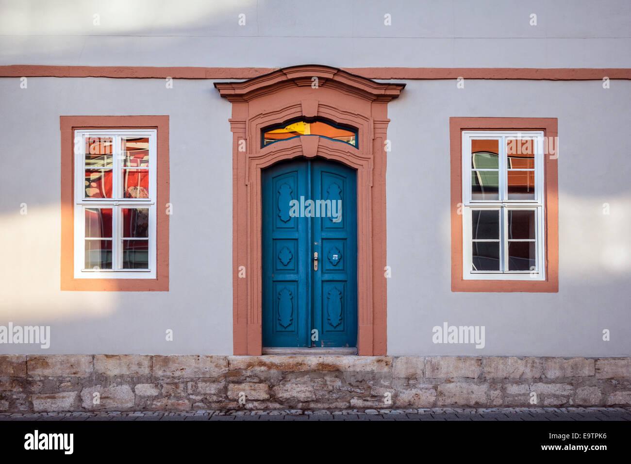 Vista frontale di una porta blu e due finestre Immagini Stock