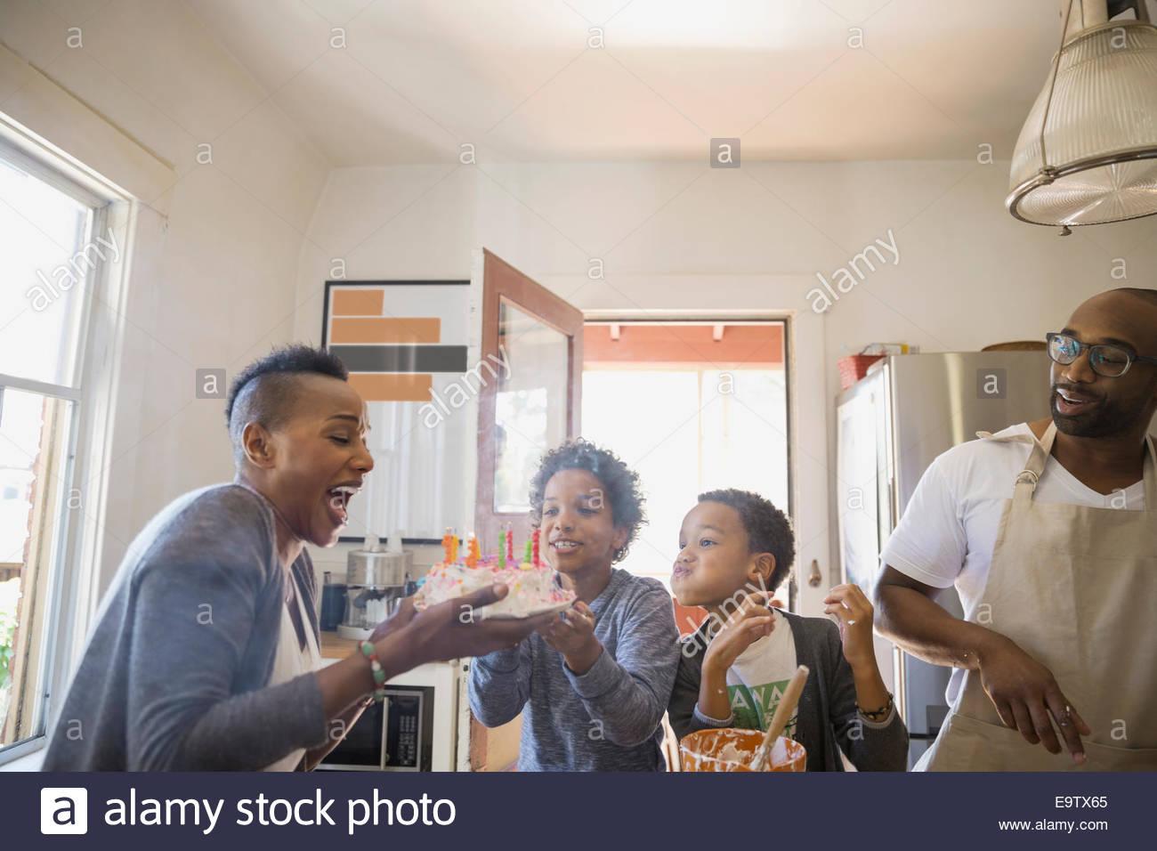 Famiglia guarda la madre soffiare la torta di compleanno candele Foto Stock
