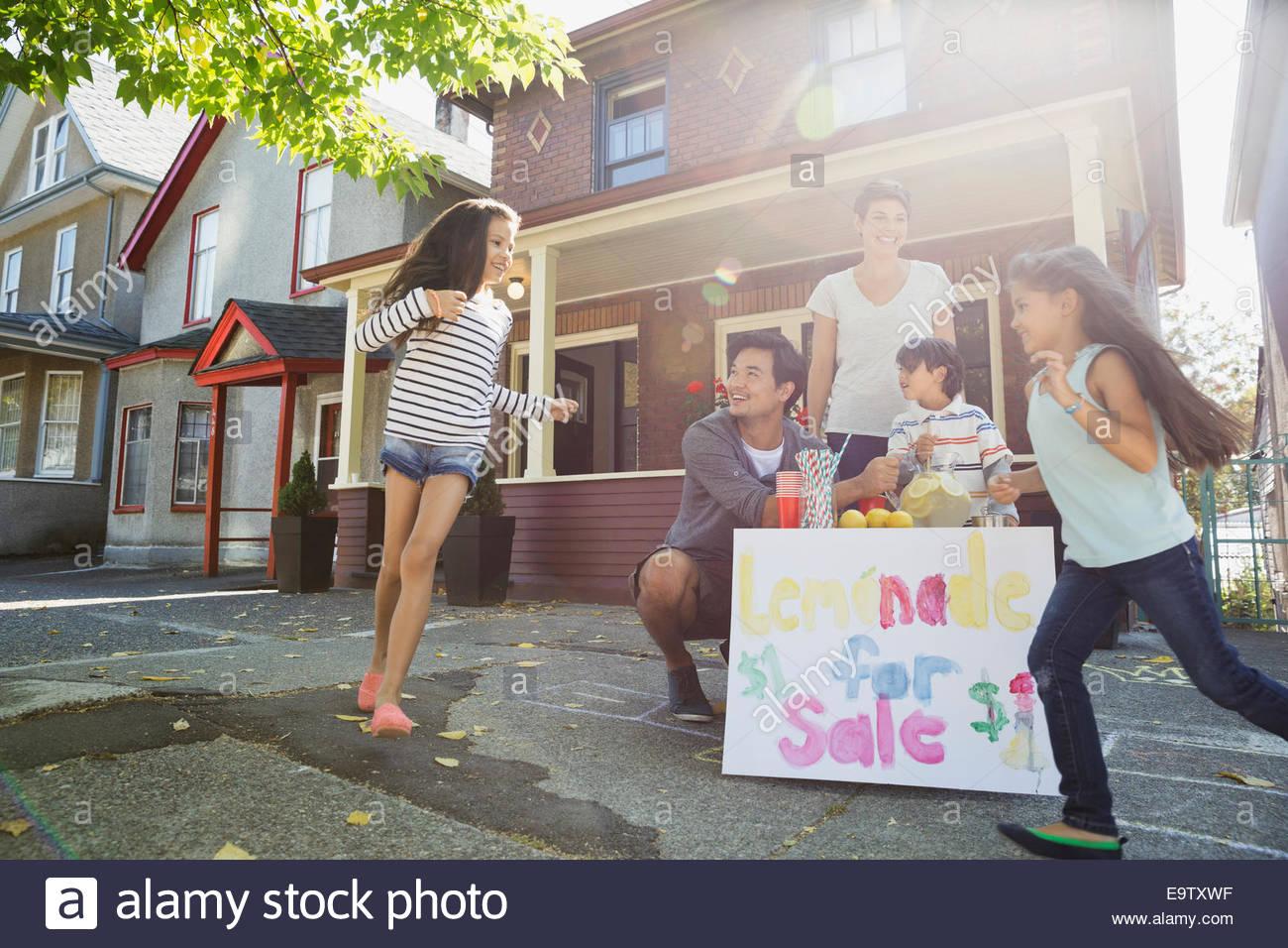 La famiglia a lemonade stand sul marciapiede fuori casa Immagini Stock