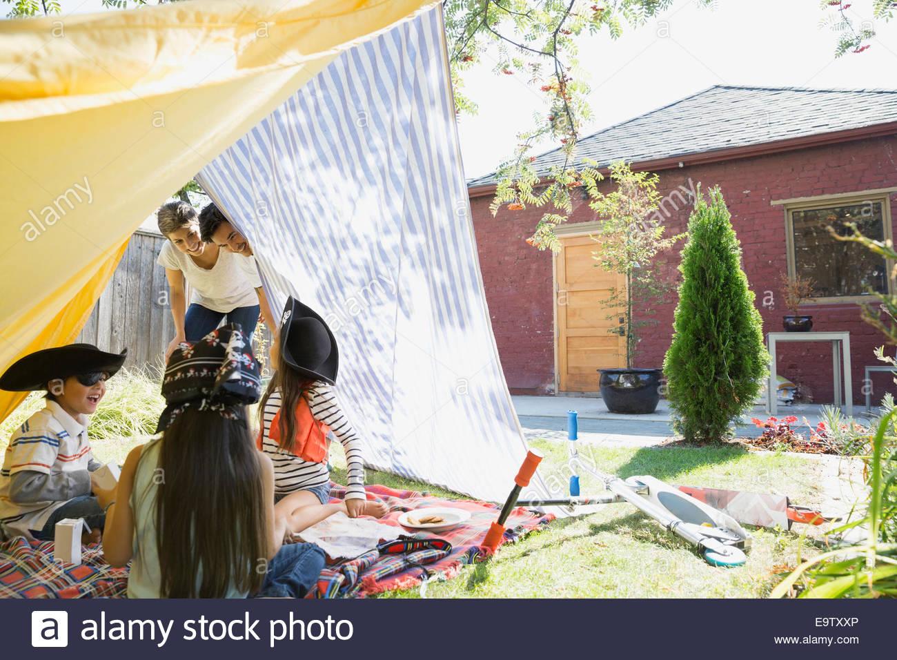 I genitori a guardare i bambini giocare i pirati in backyard fort Immagini Stock