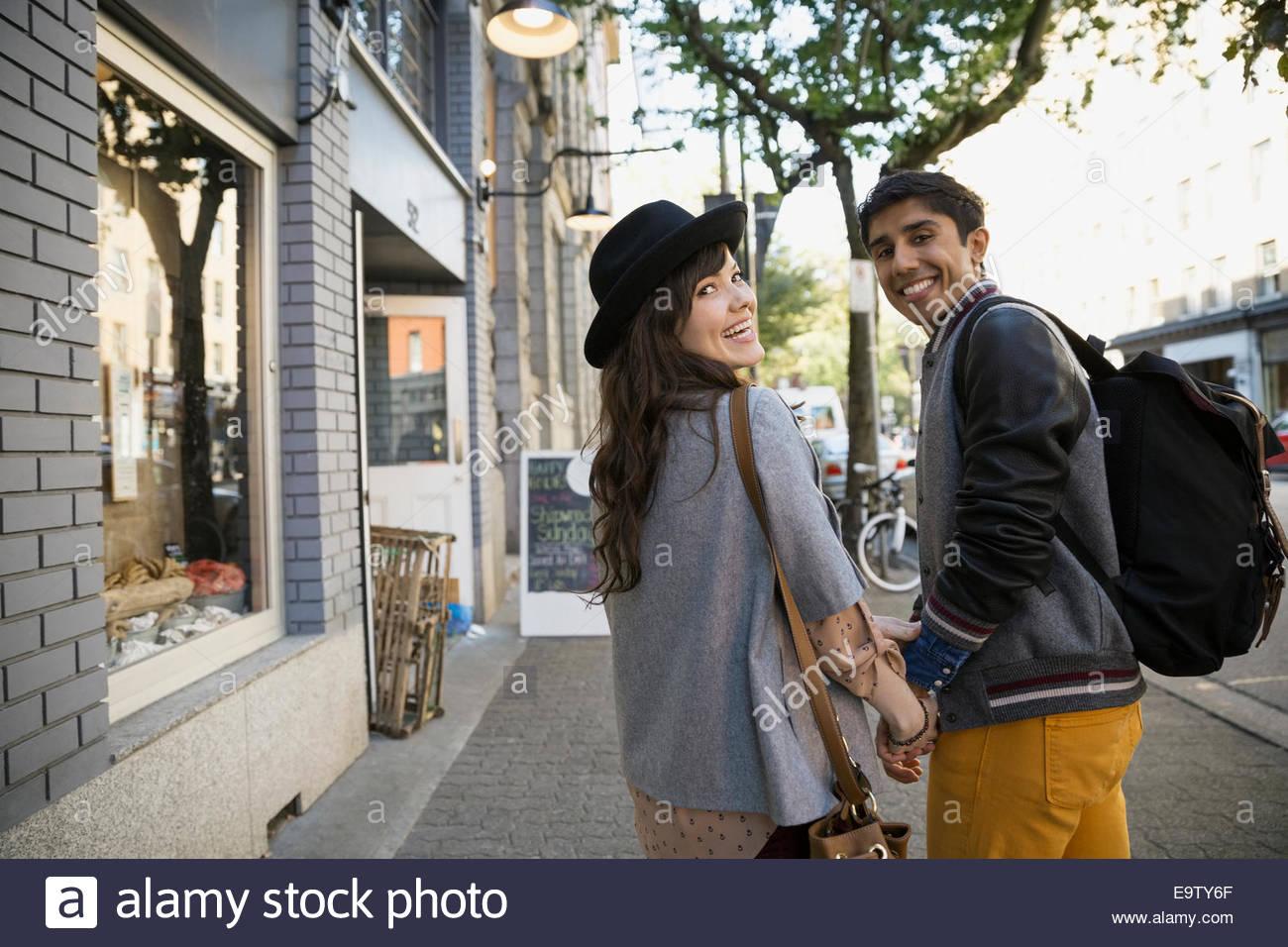 Ritratto di giovane tenendo le mani sul marciapiede urbano Immagini Stock