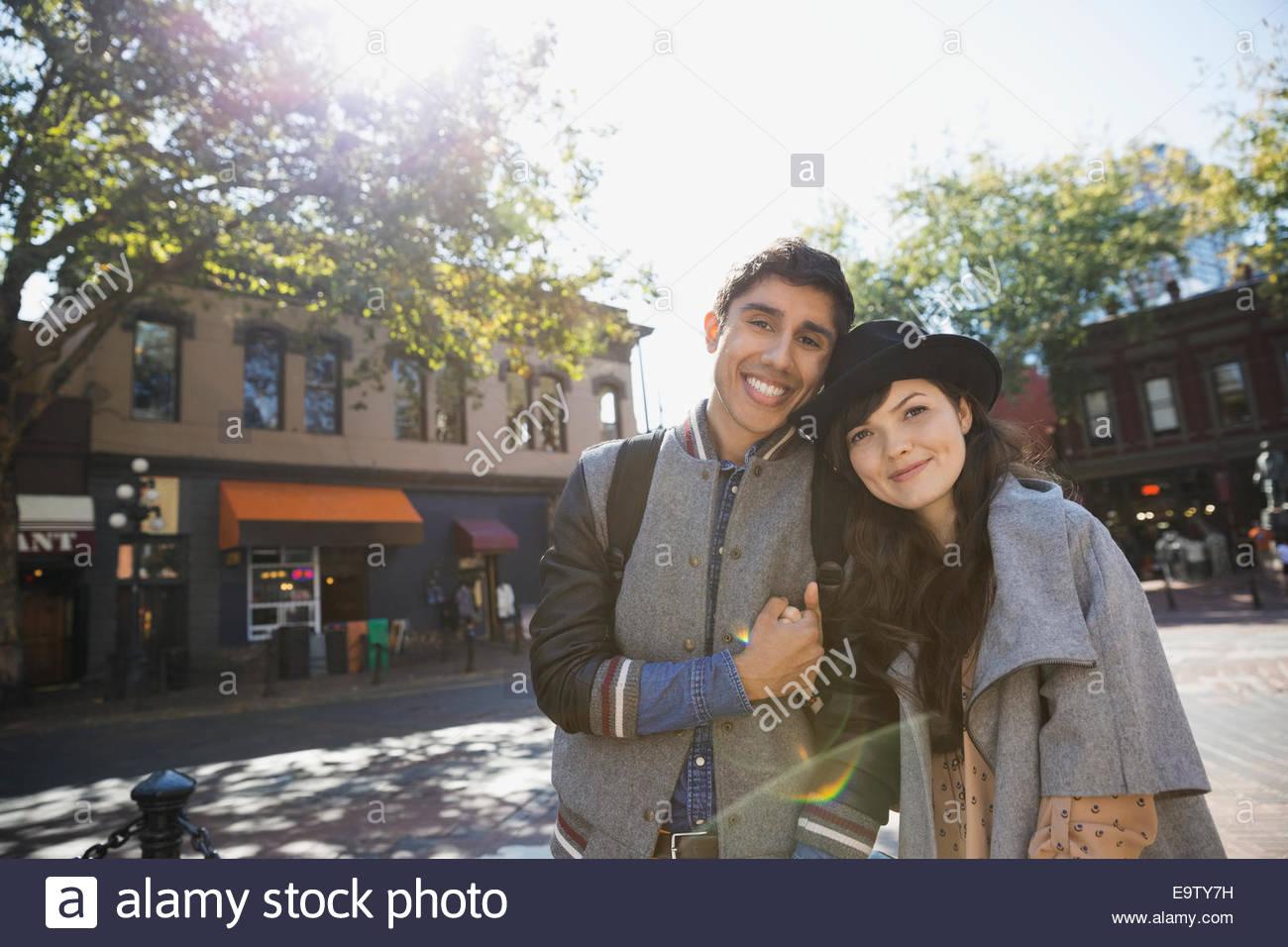 Coppia sorridente tenendo le mani sul soleggiato strada urbana Immagini Stock