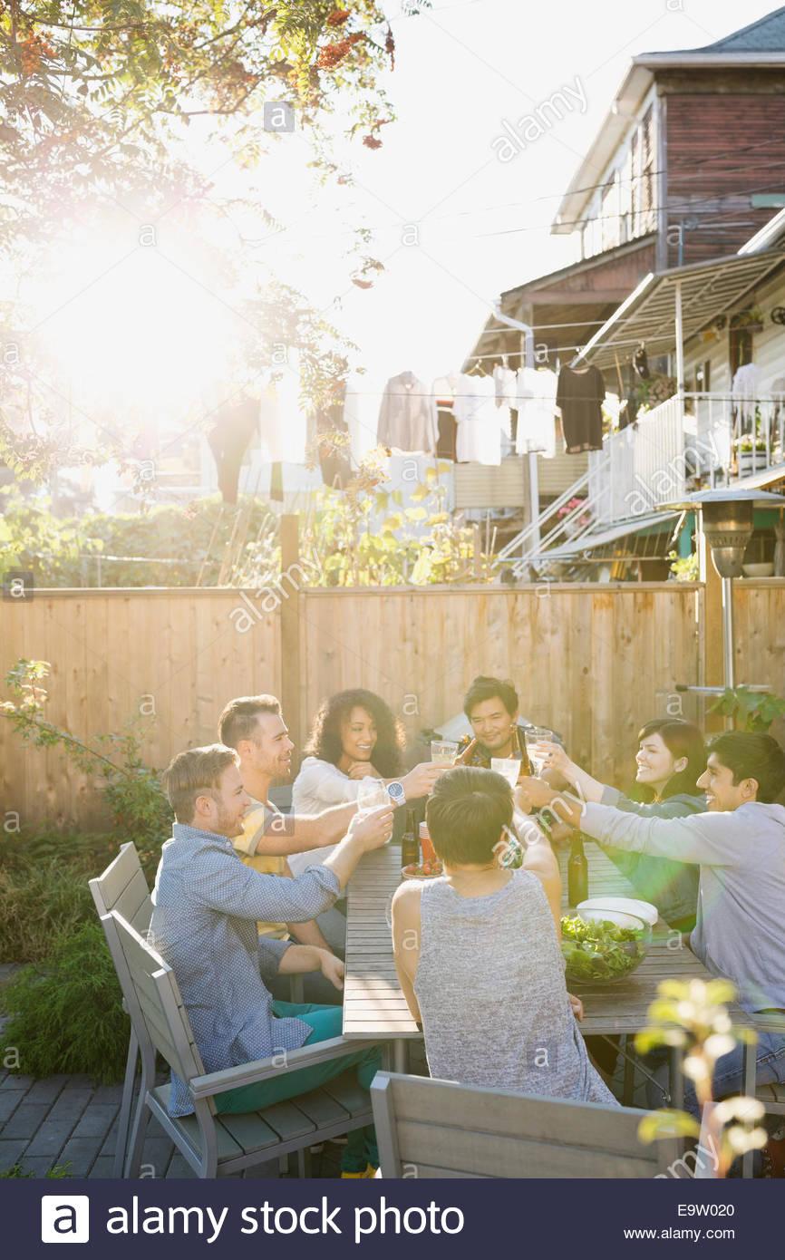 Gli amici la tostatura in backyard barbecue Immagini Stock