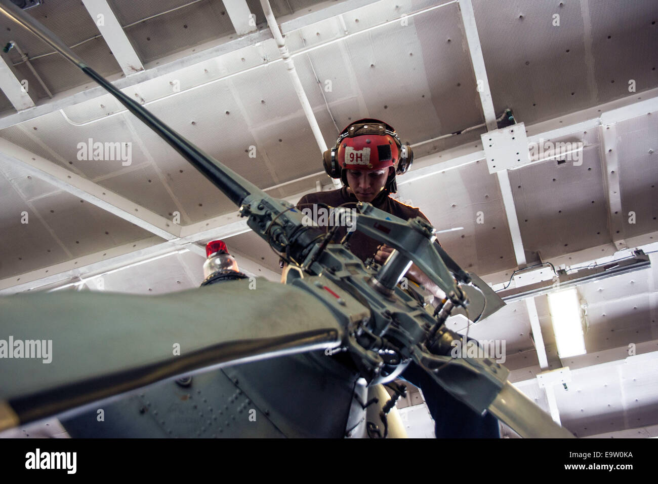 Stati Uniti Navy Airman Nathan Mitchell esegue le operazioni di manutenzione su un MH-60S Seahawk elicottero assegnato Immagini Stock