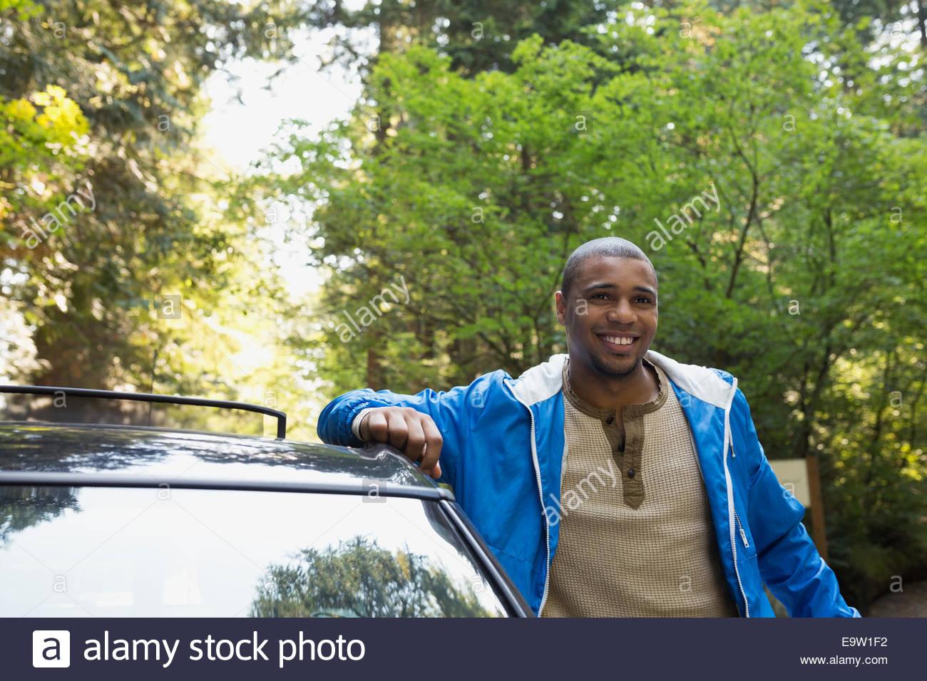 Uomo sorridente appoggiato contro auto nei boschi Immagini Stock