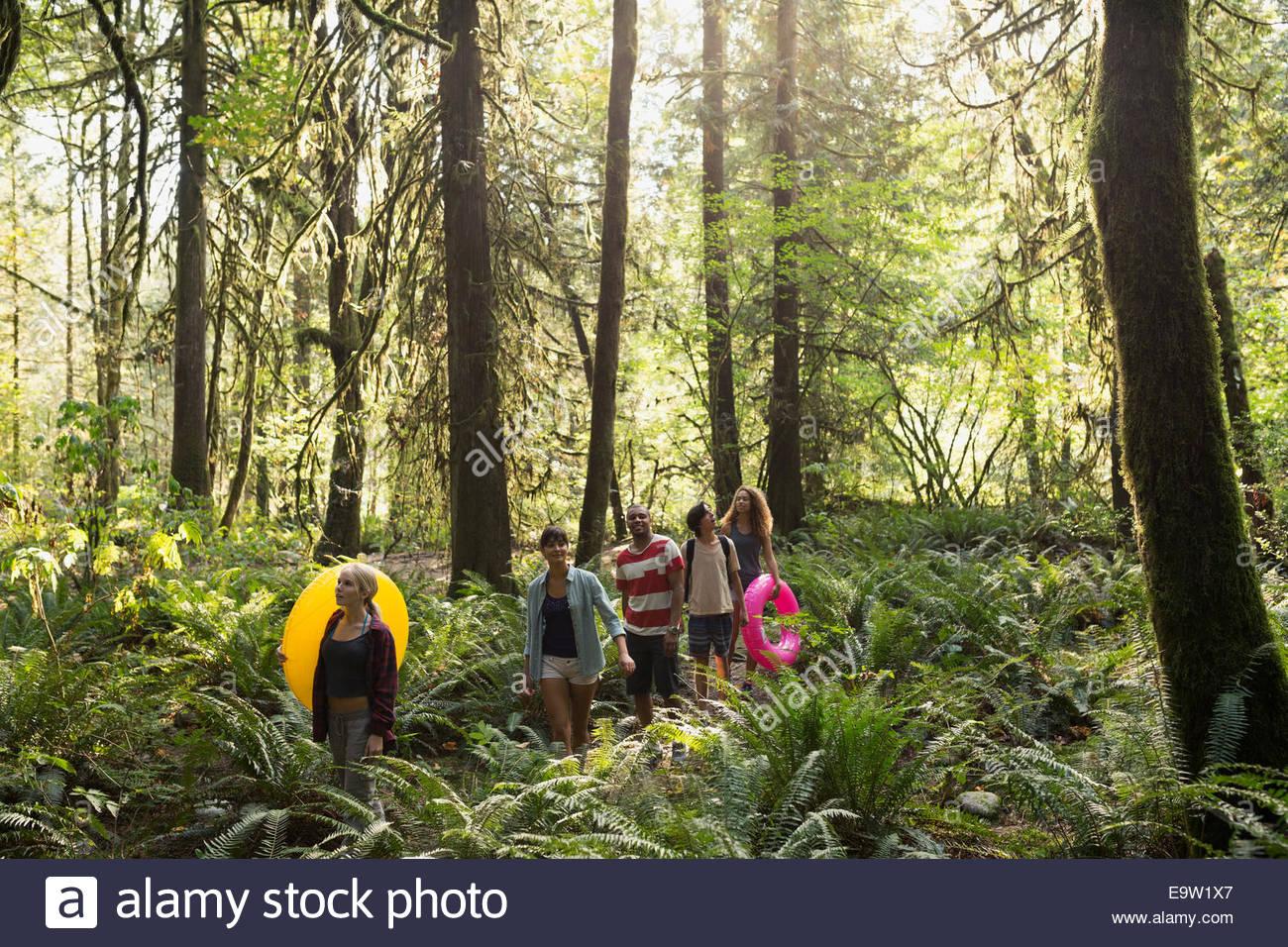 Amici con anelli gonfiabile a piedi nei boschi Immagini Stock