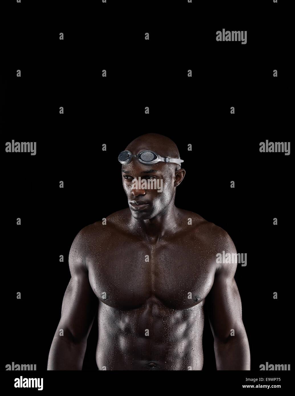 Studio shot di montare i giovani nuotatori su sfondo nero. Muscolare atleta africano che guarda lontano a copiare Immagini Stock