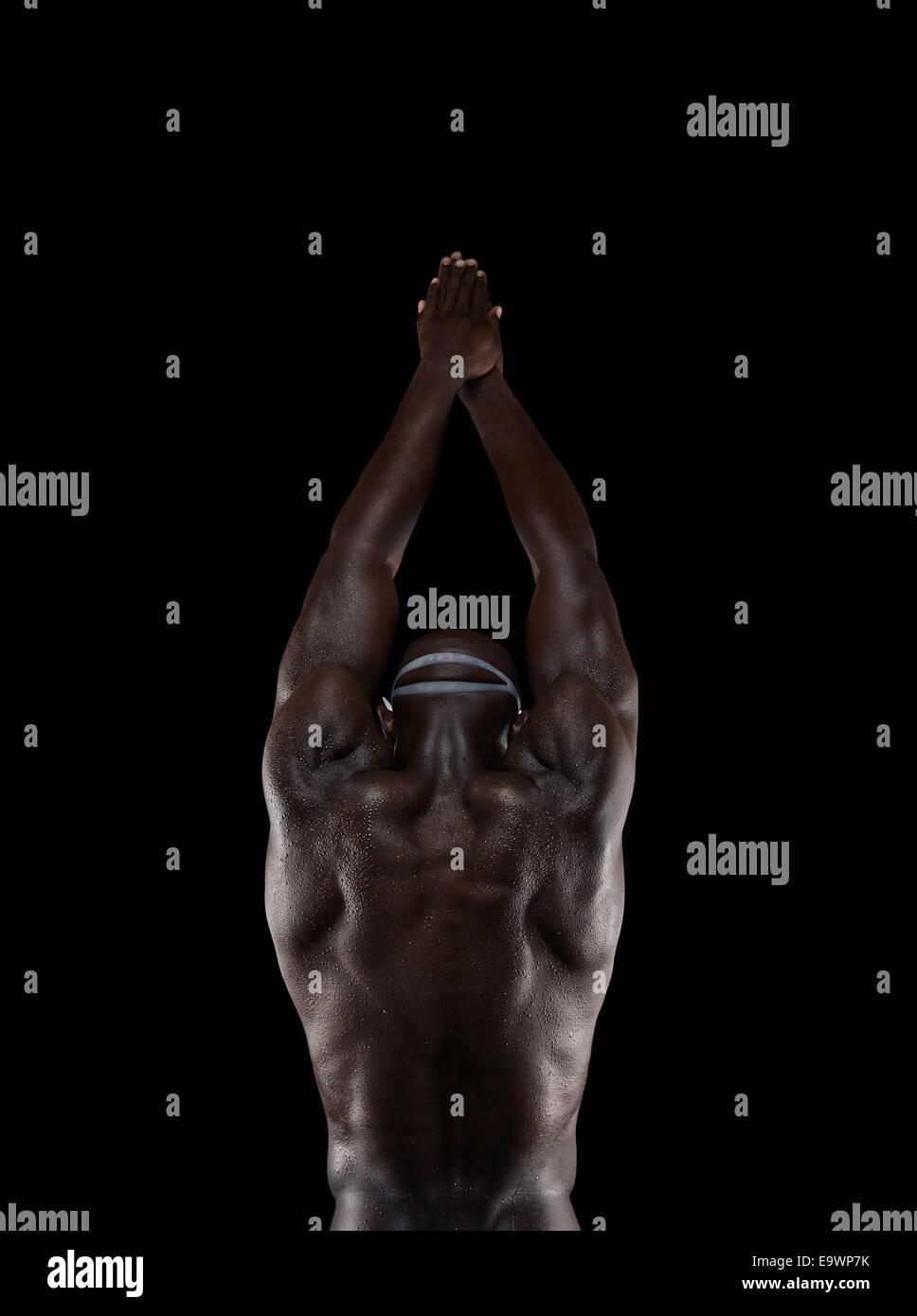 Vista posteriore del forte del giovane africano in piedi con le mani giunte sopra la sua testa. Nuotatore circa Immagini Stock