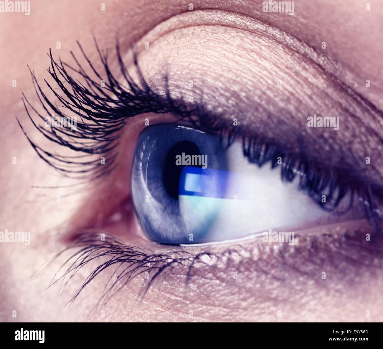 Primo piano di una giovane donna con gli occhi blu sullo schermo del computer la riflessione in esso Immagini Stock