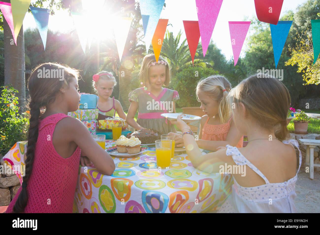 La ragazza che serve gli amici torta di compleanno Immagini Stock