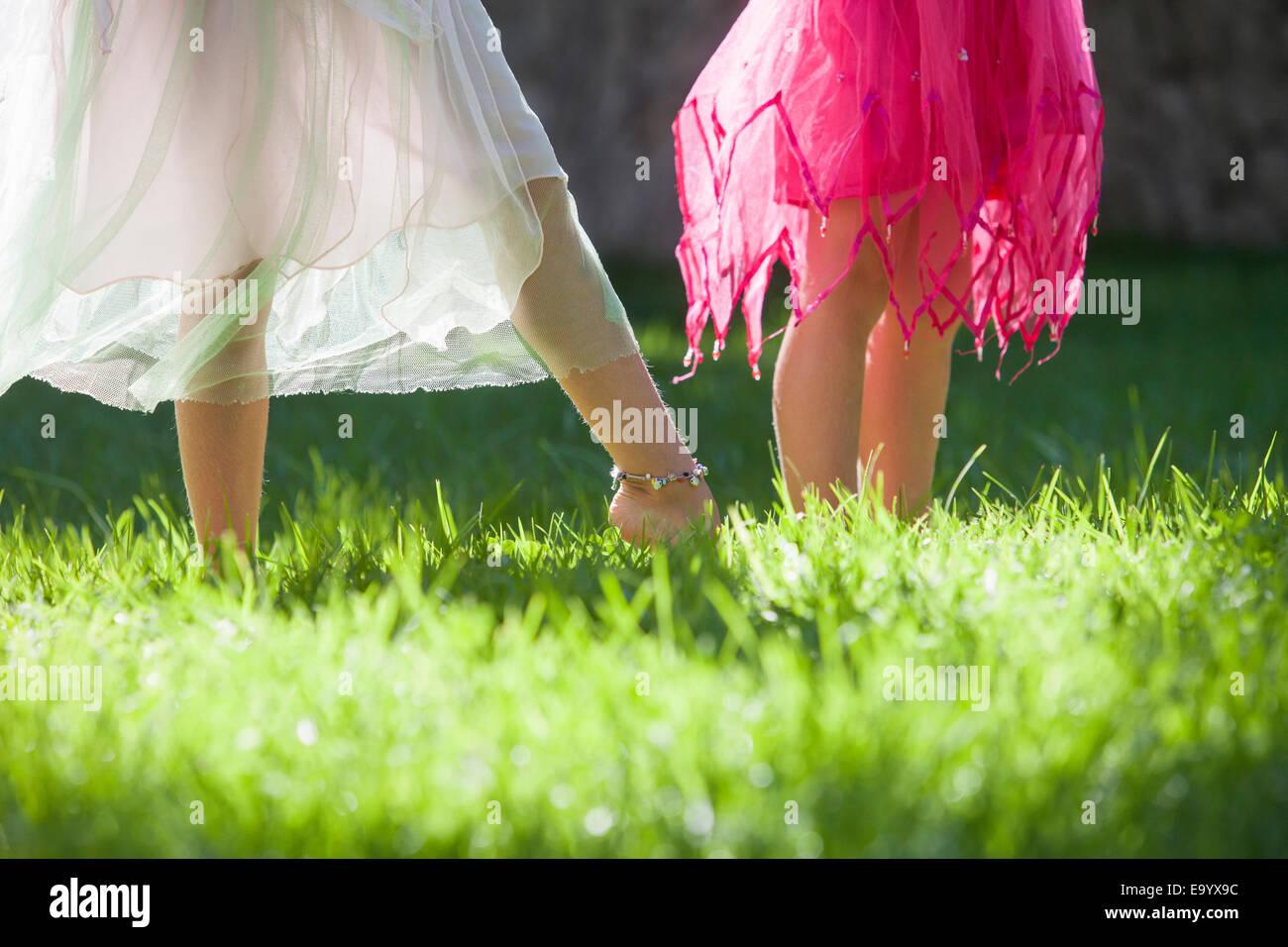 Tagliate il colpo di gambe di due ragazze in fairy costume in giardino Immagini Stock