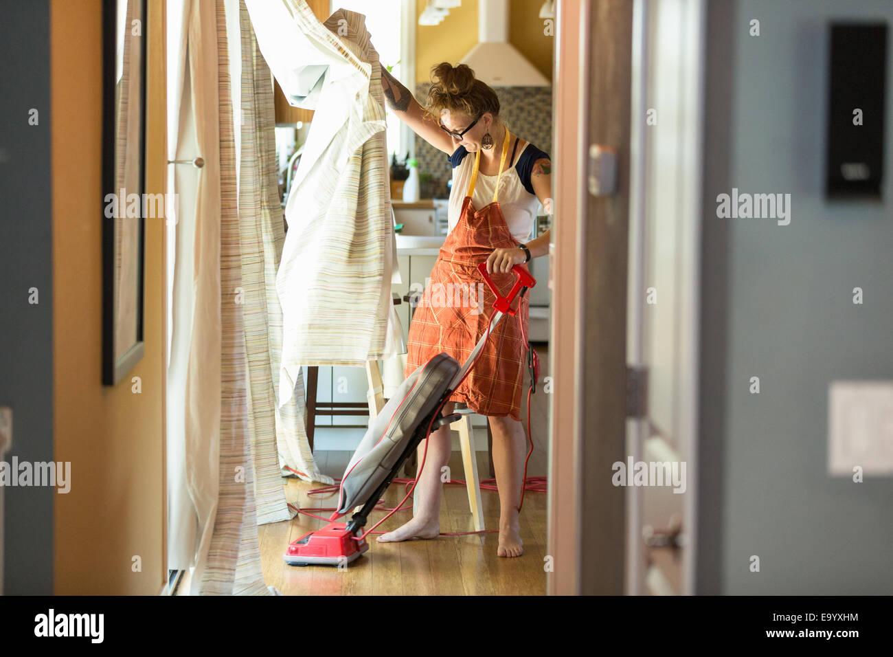 Giovane donna di aspirare con verde di prodotti per la pulizia Immagini Stock