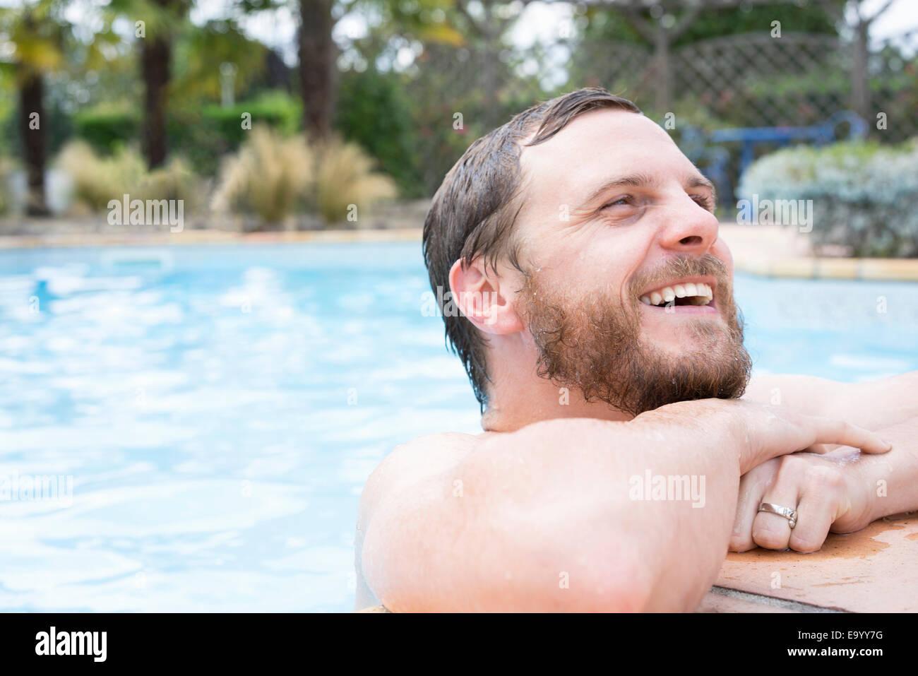 Uomo appoggiato sul bordo della piscina Immagini Stock