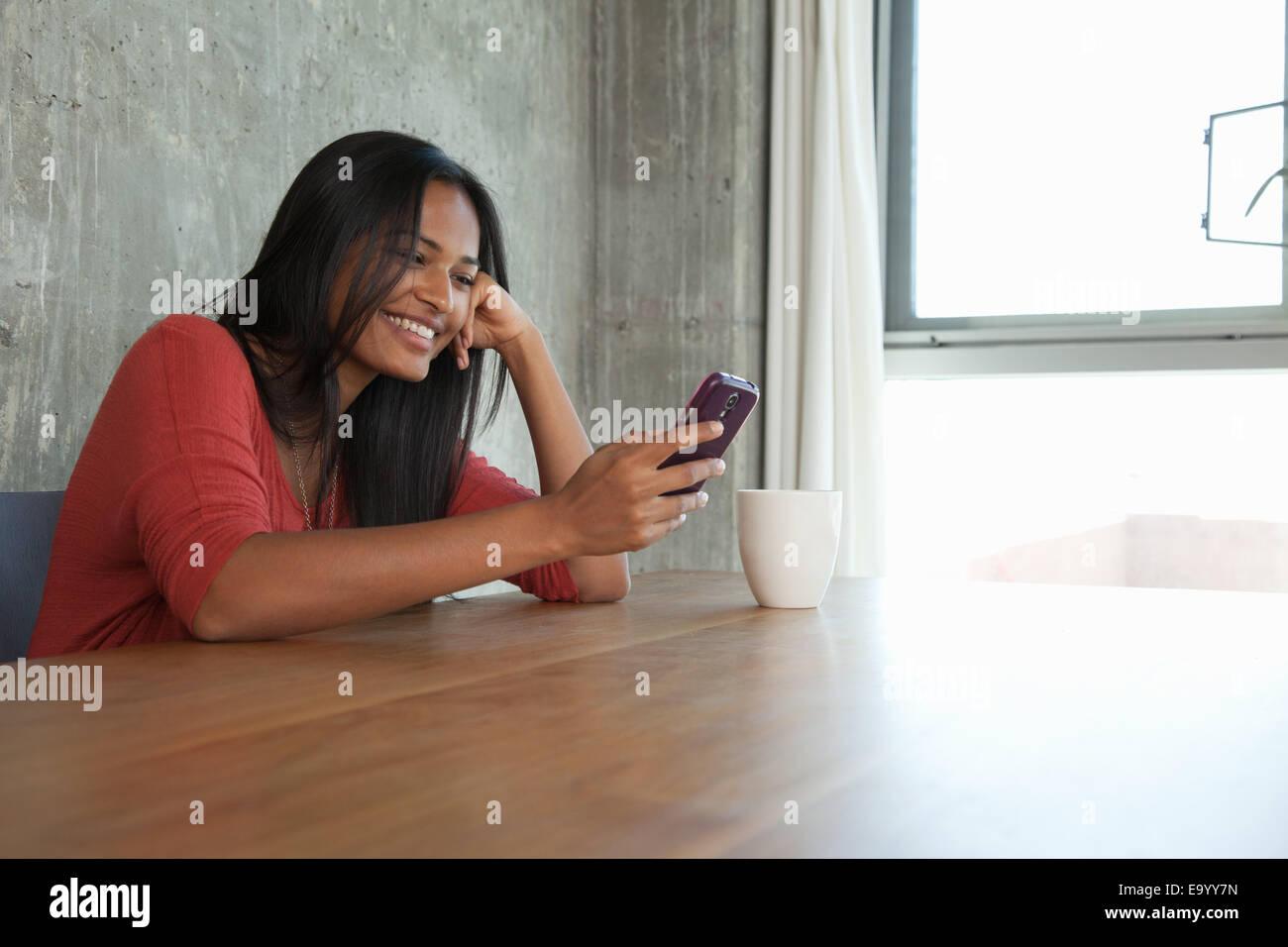 Donna che utilizza smartphone a home Immagini Stock