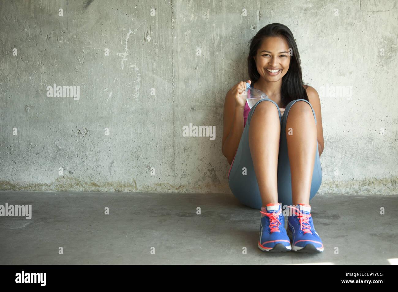 Donna con una bottiglia d'acqua seduto contro la parete Immagini Stock