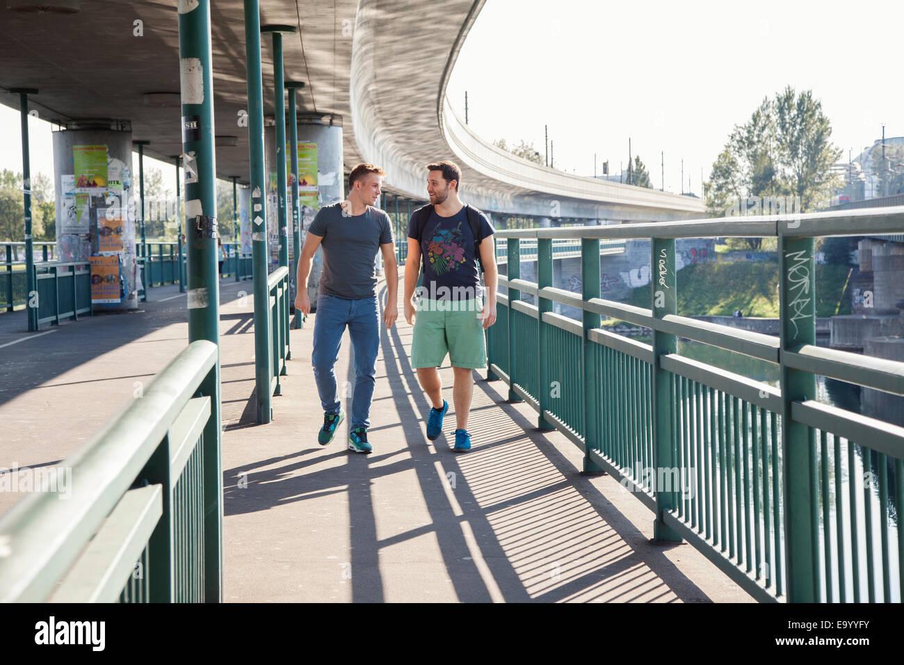 Due giovani uomini in chat come essi a piedi oltre il ponte Immagini Stock
