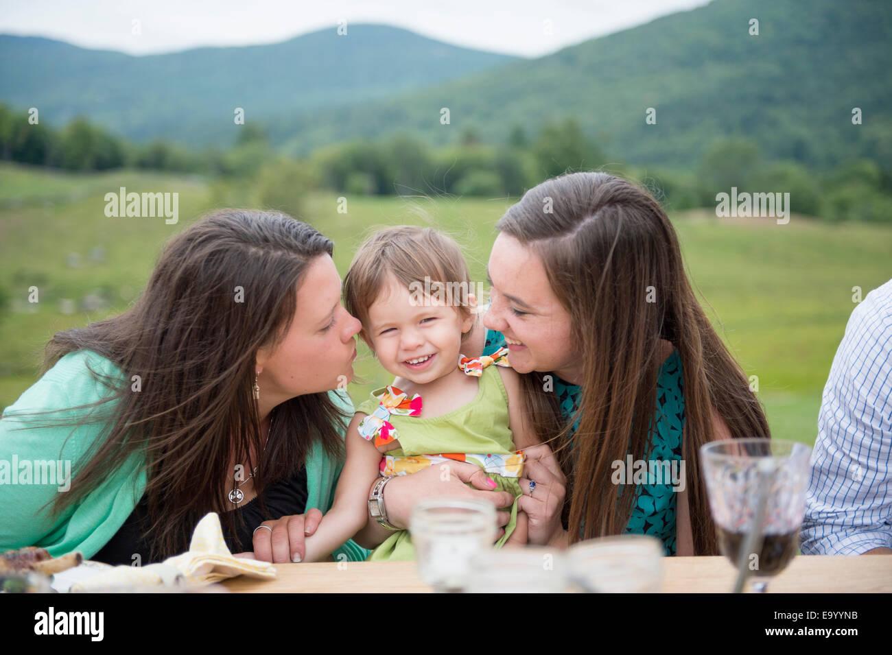 Baby ragazza seduta tra due giovani donne Immagini Stock