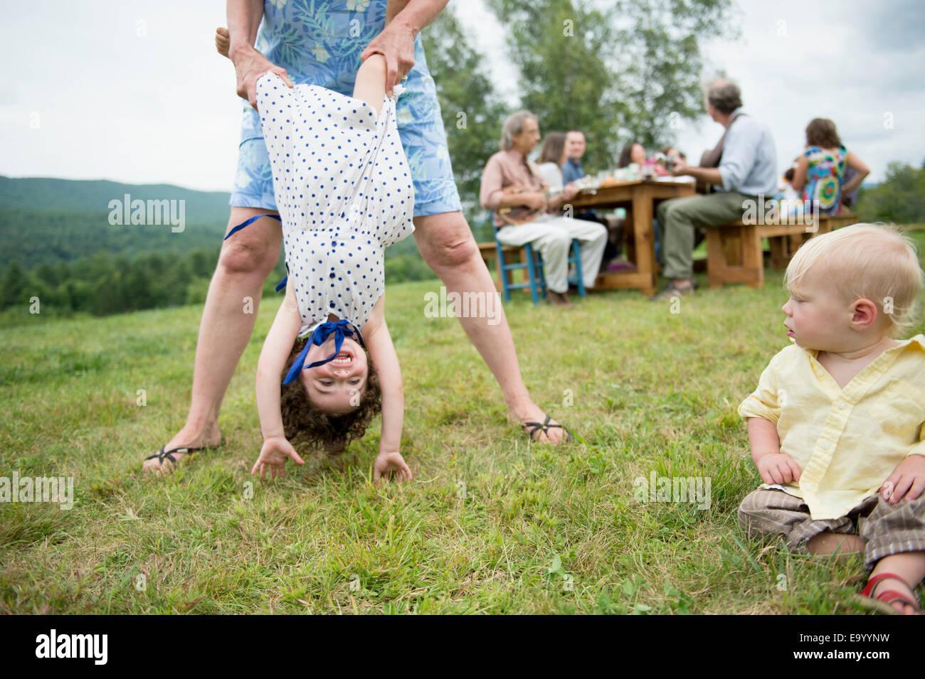 Femmina membro della famiglia scherzosamente holding toddler da gambe alla riunione di famiglia, all'aperto Foto Stock