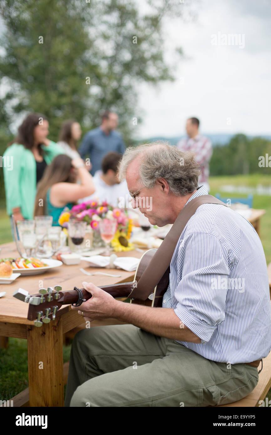 Uomo maturo a suonare la chitarra mentre gli amici e la famiglia a parlare insieme dopo un pasto all'aperto Immagini Stock