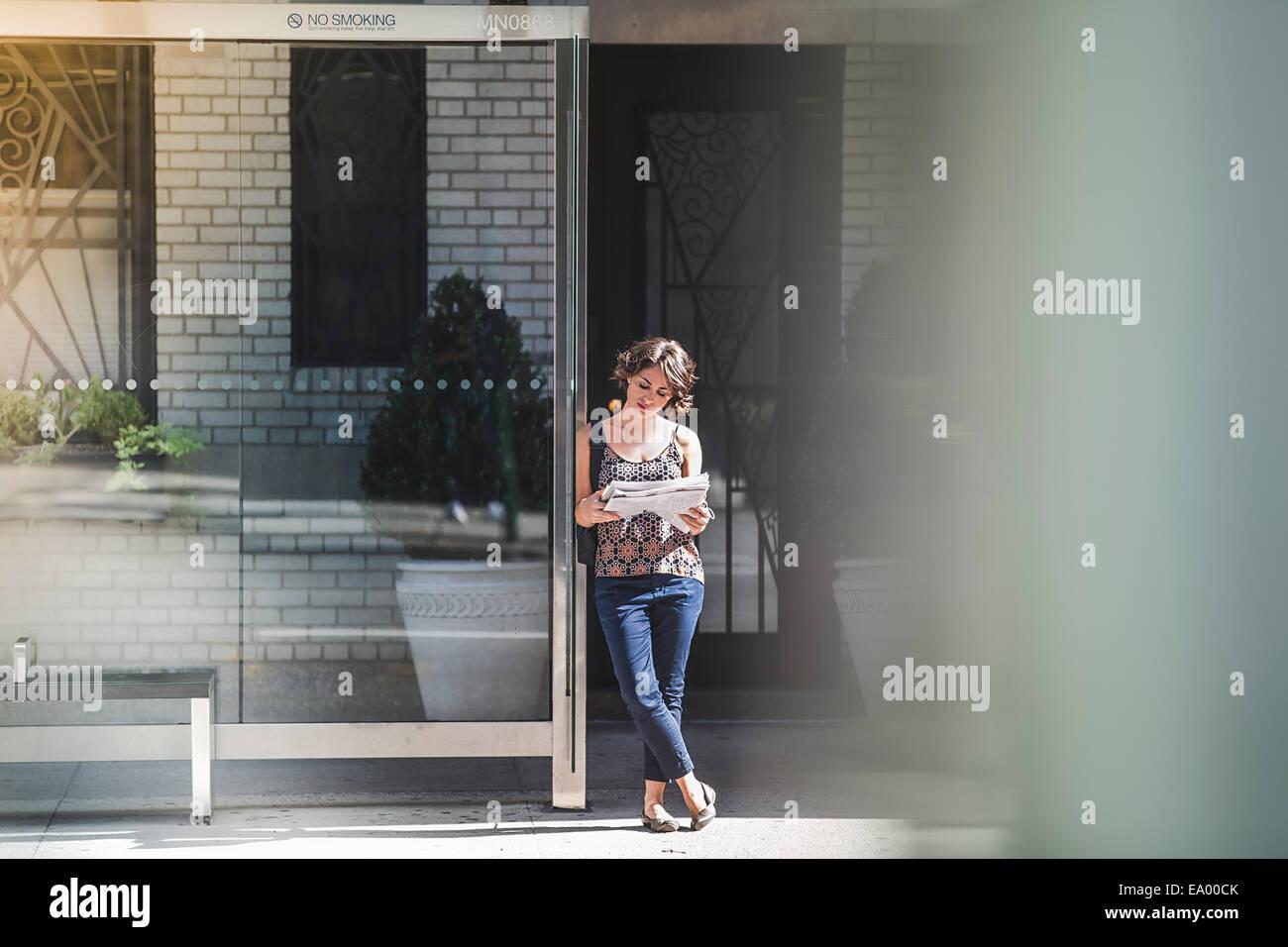 Giovane donna alla fermata bus leggendo il giornale e in attesa di bus, New York, US Immagini Stock