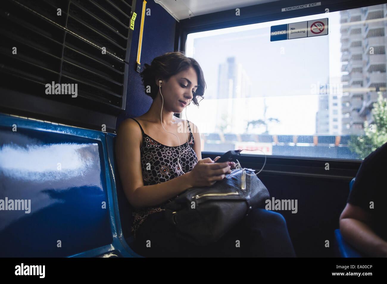 Giovane donna il pendolarismo sul bus per ascoltare musica sullo smartphone, New York, US Immagini Stock