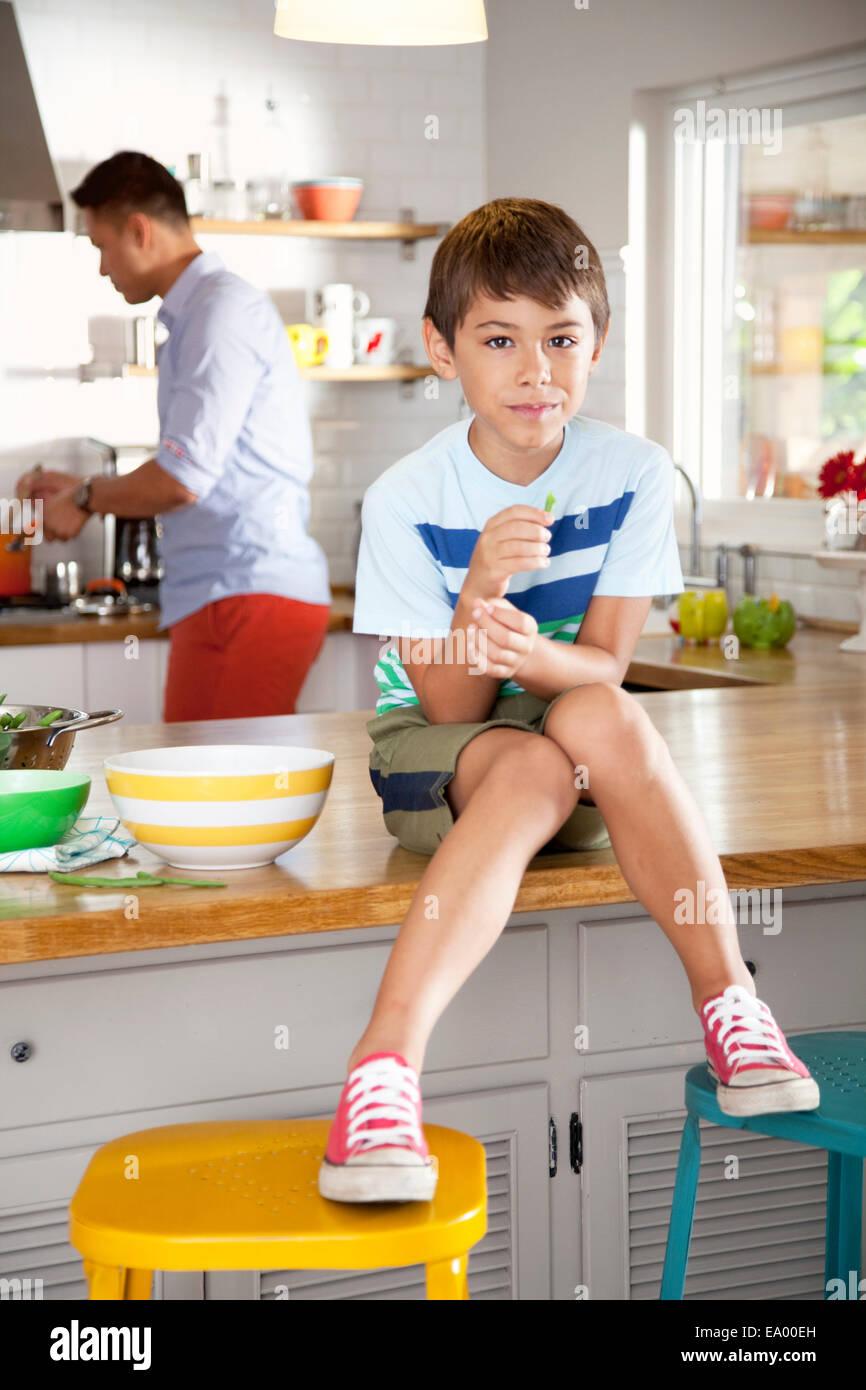 Ragazzo seduto sul banco di cucina Immagini Stock