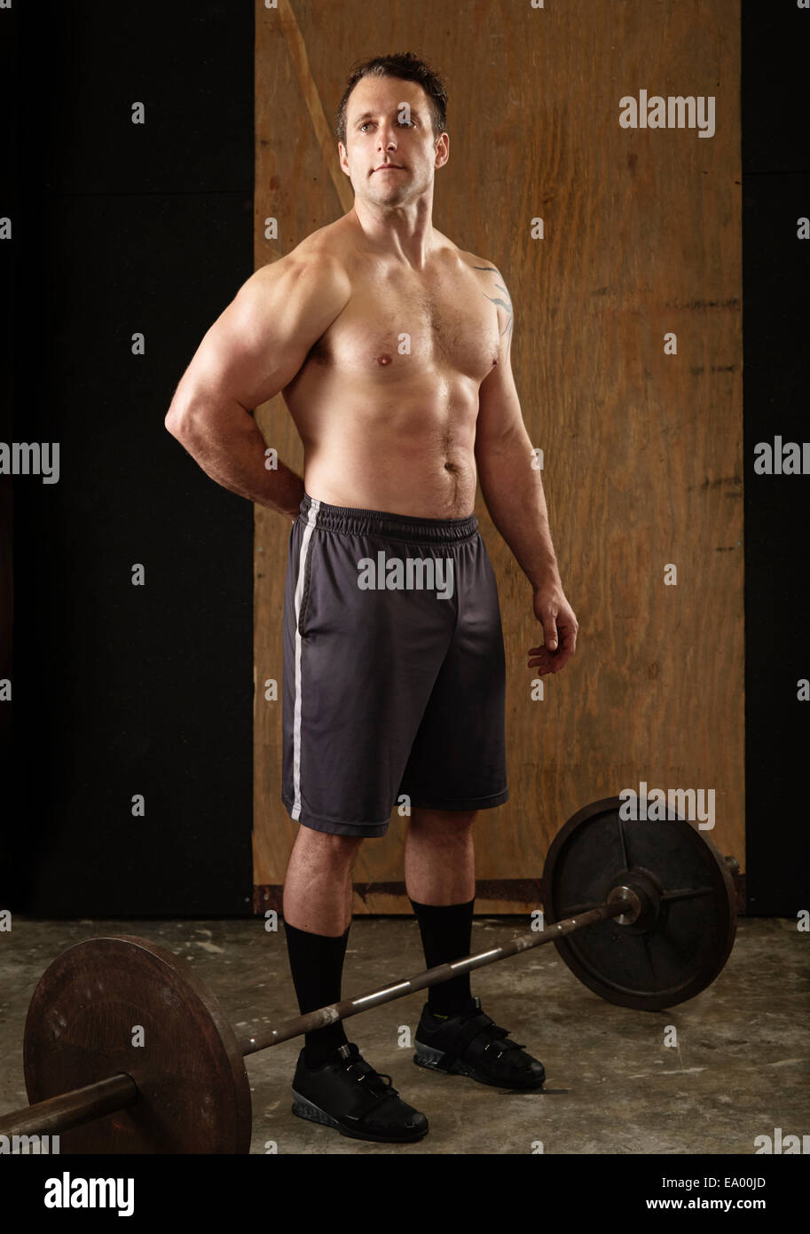 Ritratto di muscolare di metà maschio adulto weightlifter con barbell in palestra Immagini Stock