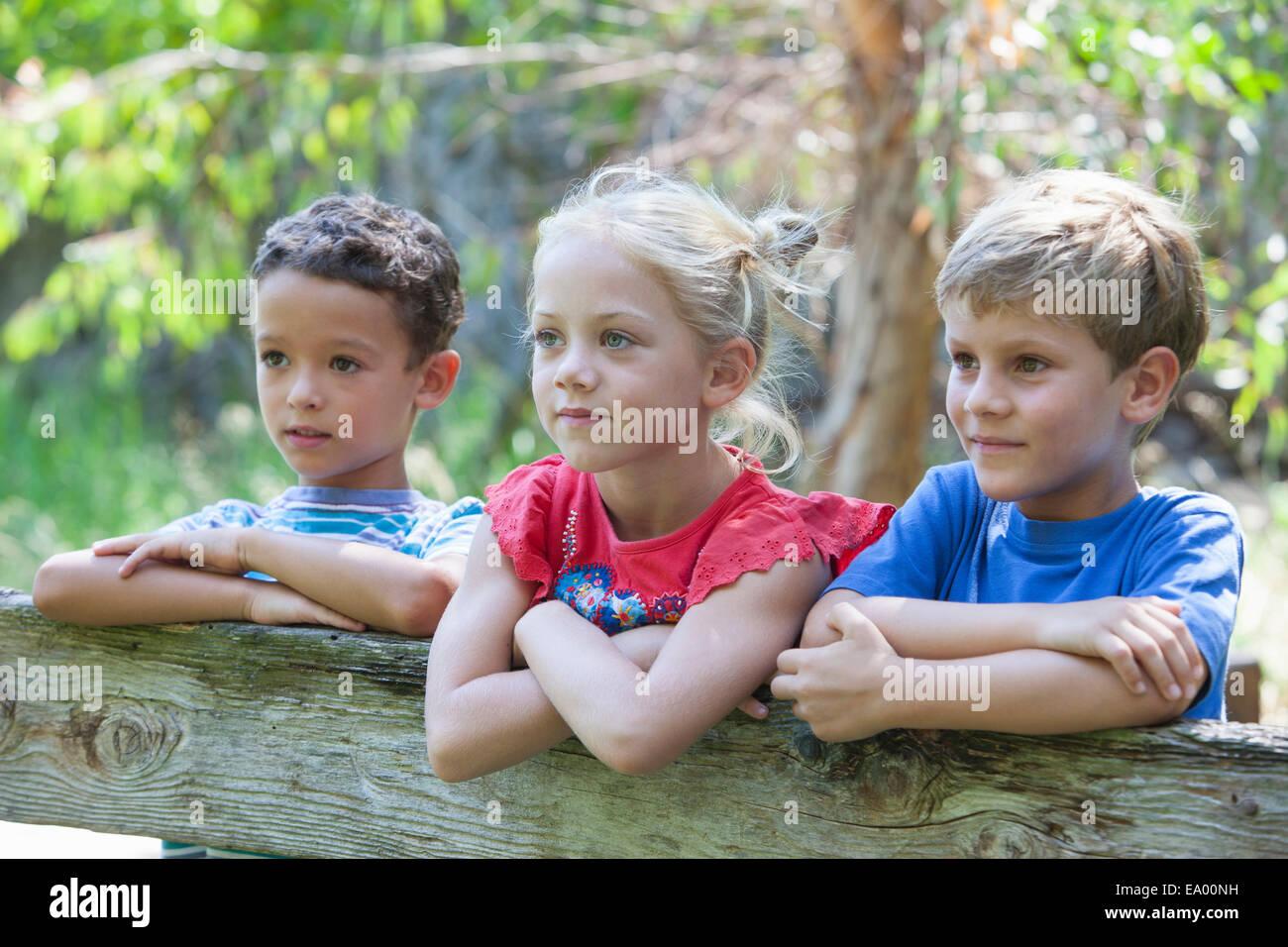 Tre bambini appoggiata sul recinto che guarda lontano Immagini Stock