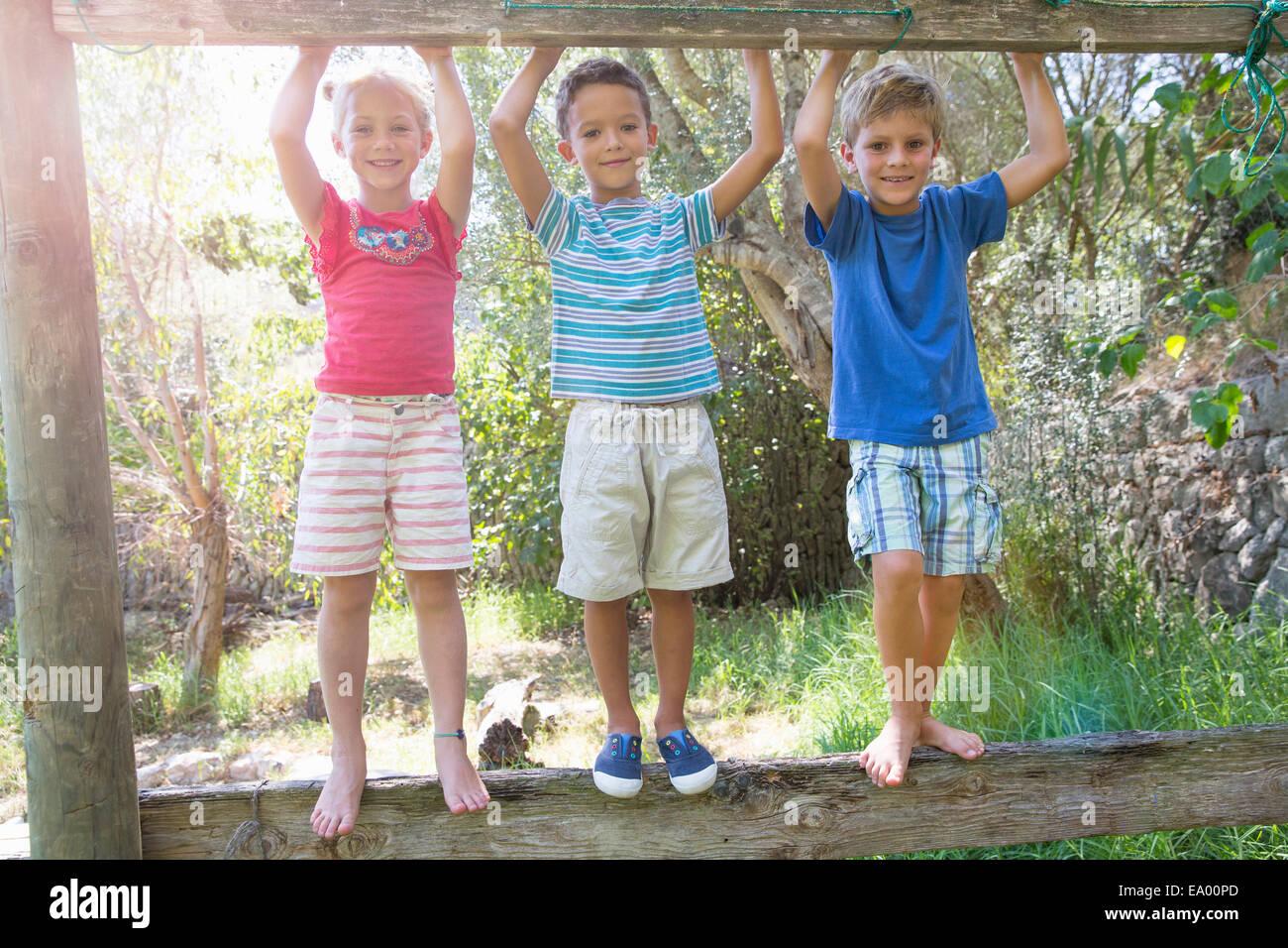 Tre bambini in giardino permanente sulla recinzione Immagini Stock