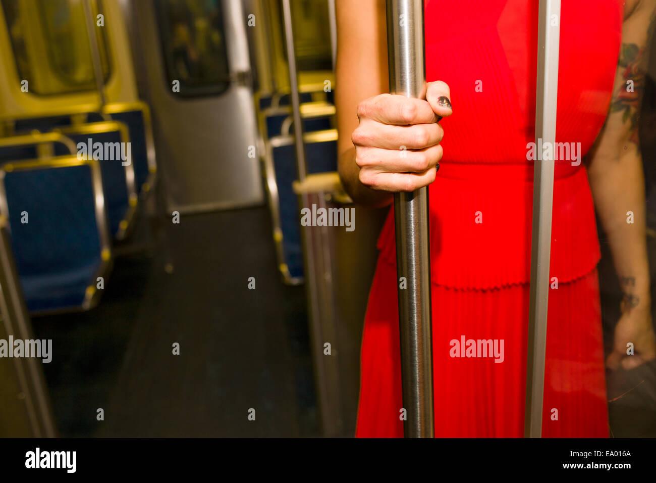 Ritagliato colpo di giovane donna indossa abito rosso sul treno della metropolitana Immagini Stock