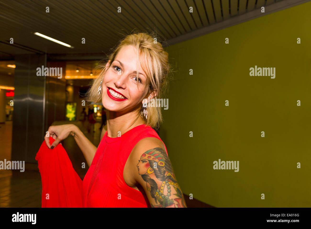Ritratto di giovane donna che indossa abito rosso nella stazione della metropolitana Immagini Stock