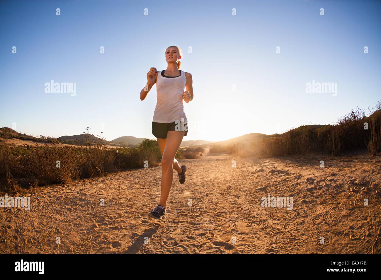 Giovane donna jogging sul percorso soleggiato, Portland, CA, Stati Uniti d'America Immagini Stock
